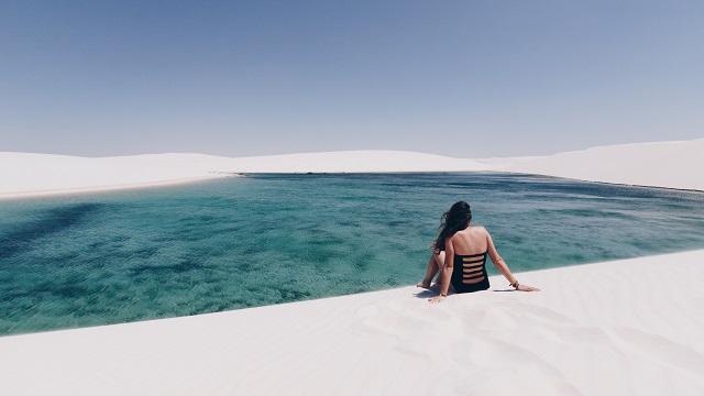 mujer frente a laguna en lençois maranhenses